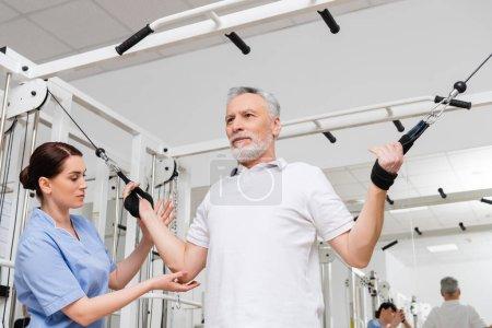 Photo pour Brunette réhabilitologue aider l'homme d'âge moyen travaillant dans la salle de gym de l'hôpital - image libre de droit