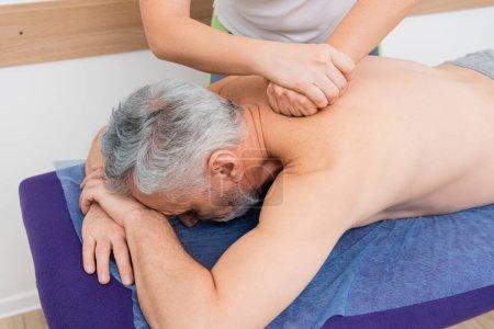 hombre maduro recibiendo masaje de espalda en el centro de rehabilitación
