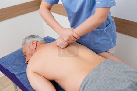 fisioterapeuta haciendo masaje de espalda a hombre maduro en el hospital