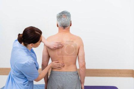 Foto de Vista posterior del hombre maduro cerca del ortopedista examinándolo en el hospital - Imagen libre de derechos
