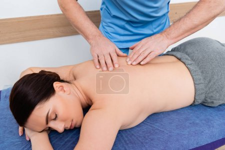 physiotherapist doing back massage to brunette woman in clinic