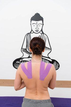 Photo pour Vue arrière de la femme debout devant budda dessin sur le mur pendant la kinésithérapie - image libre de droit
