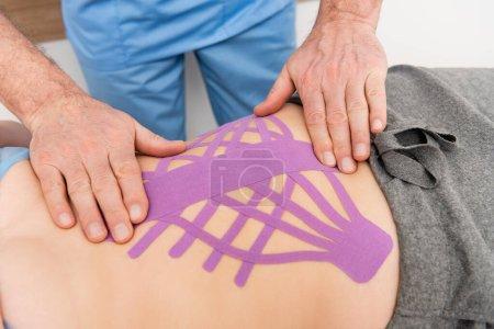 Photo pour Vue partielle du réhabilitologue effectuant la procédure de kinésiotaping sur la femme en clinique - image libre de droit