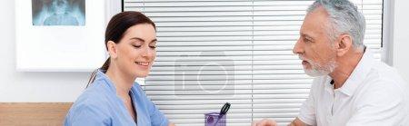 Photo pour Homme mûr parler à un réhabilitologue souriant pendant la consultation, bannière - image libre de droit