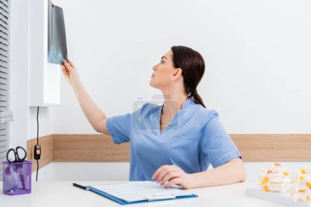 Photo for Brunette rehabilitologist looking at x-ray while sitting near clipboard - Royalty Free Image