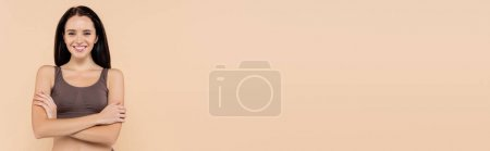 Photo for Happy, brunette woman posing with crossed arms isolated on beige, banner - Royalty Free Image