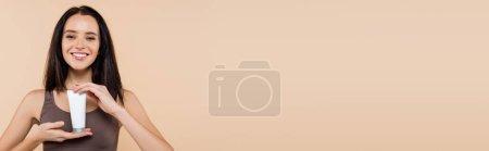 Photo pour Jeune femme souriant à la caméra tout en tenant la crème cosmétique isolée sur beige, bannière - image libre de droit