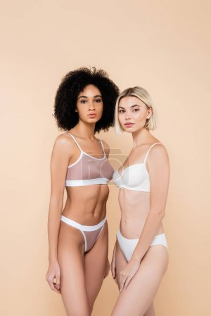young interracial women in underwear looking at camera isolated on beige
