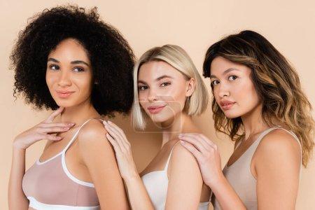 young interracial women in underwear posing on beige