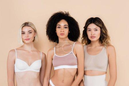 pretty multiethnic women in bras looking at camera on beige