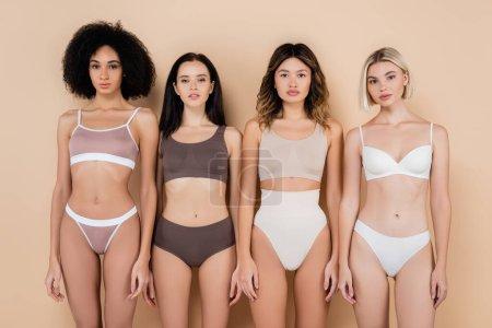 front view of pretty multiethnic women in underwear looking at camera on beige