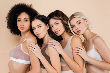 pretty multiethnic women leaning on each other while looking at camera on beige