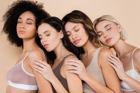 Photo pour Jeune femme multiculturelle s'appuyant les uns sur les autres avec les yeux fermés isolés sur beige - image libre de droit