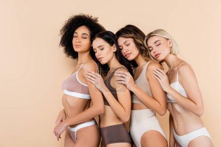 Foto de Mujeres multiculturales en ropa interior apoyados uno en el otro con los ojos cerrados en beige - Imagen libre de derechos
