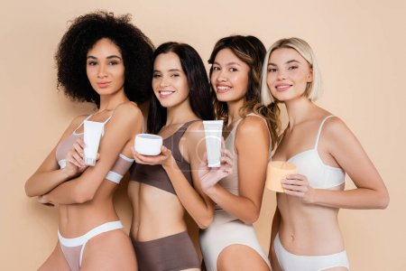 sexy multiethnic women holding body cream while smiling at camera on beige