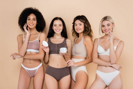 Photo for Young woman holding cosmetic cream near pretty interracial friends on beige - Royalty Free Image