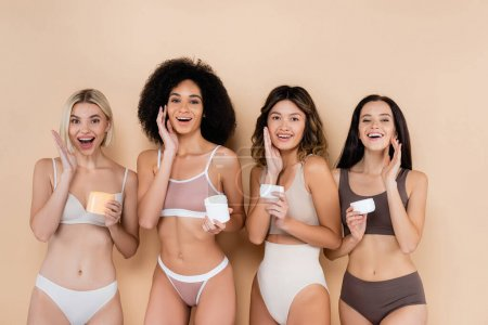 Photo for Amazed interracial women in underwear applying face cream on beige - Royalty Free Image