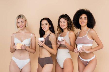 sexy interracial women in underwear holding body cream on beige
