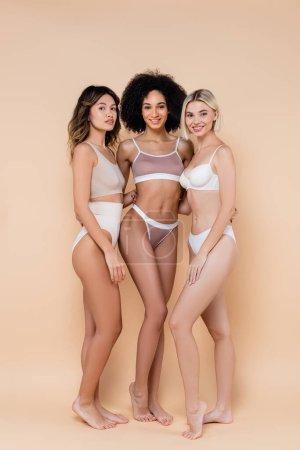 full length view of barefoot interracial women posing in underwear on beige