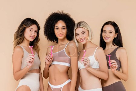 young multicultural women in underwear holding safety razors on beige