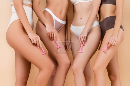 Photo for Cropped view of sexy women posing with safety razors on beige - Royalty Free Image