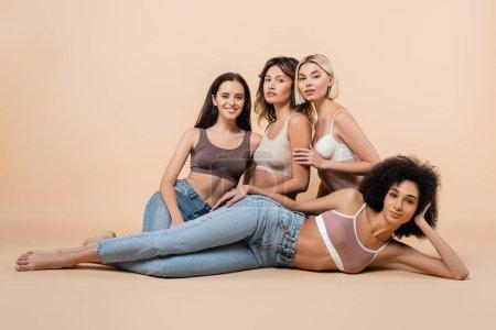 Foto de Africano americano mujer en sujetador y jeans acostado cerca interracial amigos en beige - Imagen libre de derechos
