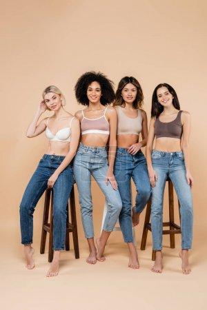 pretty multiethnic women in jeans and bras posing near high stools on beige
