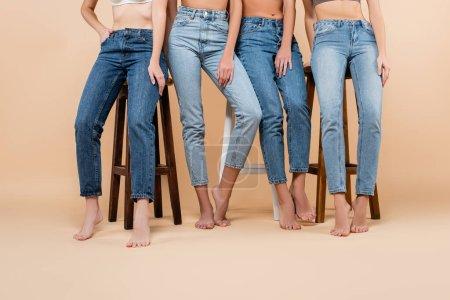 Photo pour Vue partielle de femmes pieds nus en jeans posant près de hauts tabourets sur beige - image libre de droit