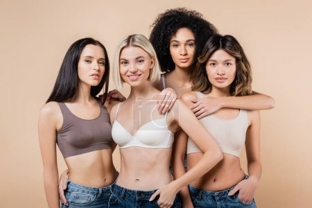 young multicultural women in bras and jeans looking at camera isolated on beige