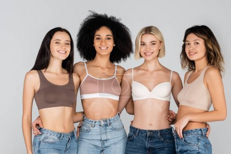 Photo for Smiling interracial women in bras and jeans embracing while looking at camera isolated on grey - Royalty Free Image