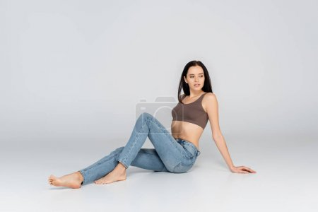 brunette woman with perfect body sitting on grey in jeans and bra