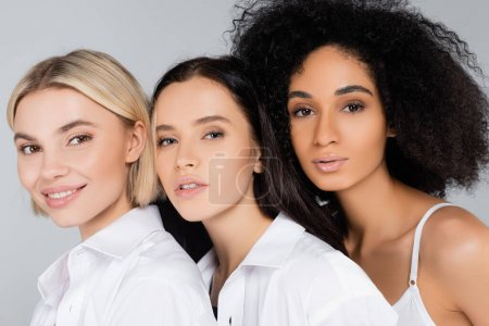 young interracial women with perfect skin looking at camera isolated on grey