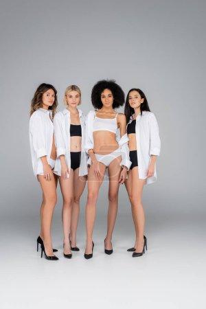Foto de Vista completa de las mujeres interracial sexy en ropa interior y camisas blancas en gris - Imagen libre de derechos