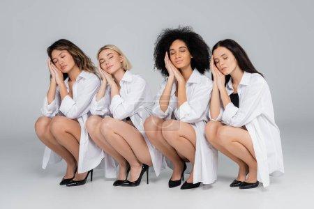 Frauen in weißen Hemden und Schuhen halten sich die Hände vors Gesicht, während sie mit geschlossenen Augen auf grau posieren