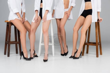 partial view of women in shoes, panties and shirts posing near high stools on grey