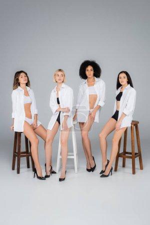 Photo pour Femmes multiculturelles avec des corps parfaits posant près de hautes selles sur gris - image libre de droit