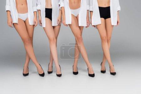 vista parcial de mujeres delgadas en camisas, bragas y zapatos de pie sobre gris