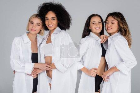 Photo pour Heureux amis multiethniques en sous-vêtements et chemises blanches embrassant isolé sur gris - image libre de droit