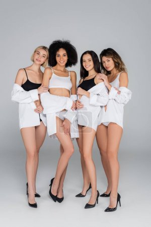 happy interracial women smiling at camera while posing in underwear and white shirts on grey