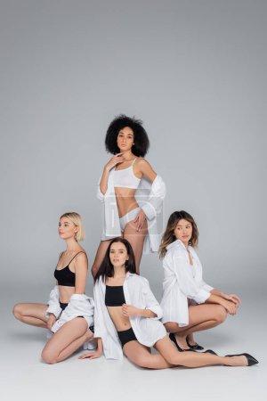 Photo pour Sexy afro-américaine femme debout près d'amis multiethniques posant sur gris - image libre de droit