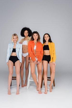 Foto de Sexy interracial las mujeres en ropa interior y camisas mirando la cámara cerca de alto taburetes en gris - Imagen libre de derechos