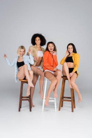 Photo pour Excité interracial femmes en sous-vêtements et chemises posant sur de hauts tabourets sur gris - image libre de droit