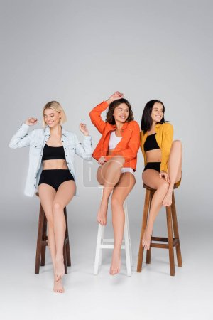 cheerful multiethnic women in shirts and underwear sitting on high stools on grey