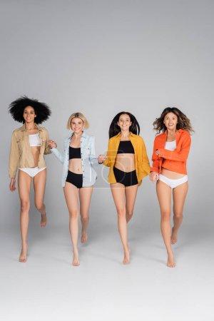 glückliche multikulturelle Frauen in Hemden und Unterwäsche, die Händchen halten, während sie auf grau gehen