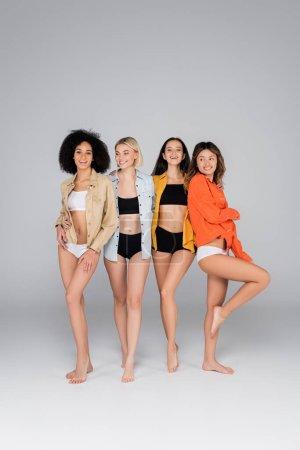 joyful interracial women in shirts and underwear standing on grey