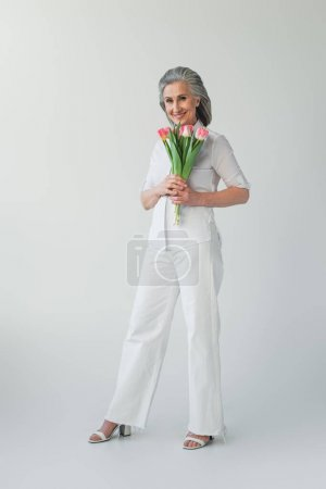 Photo for Mature woman smiling while holding flowers on grey background - Royalty Free Image