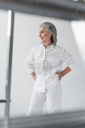 Photo pour Femme d'âge moyen souriante avec les mains sur les hanches près des tuyaux métalliques sur fond gris - image libre de droit