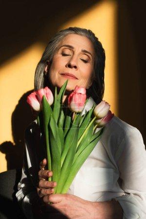Femme mûre avec les yeux fermés tenant des tulipes sur fond jaune avec ombre