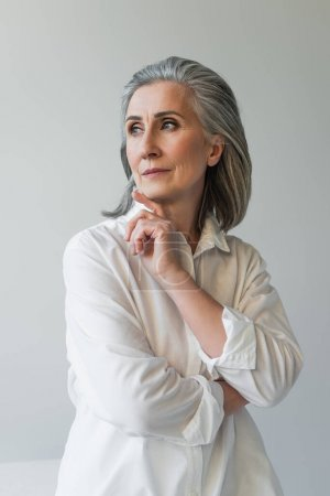 Mature woman with hand near chin posing isolated on grey