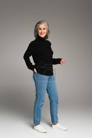Smiling mature woman holding hand in pocket of jeans on grey background